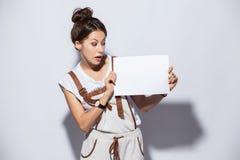 Lächelnde junge hübsche Frau, die leeres Schild, über dem weißen Hintergrund lokalisiert zeigt lizenzfreie stockfotografie