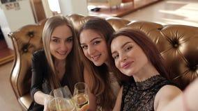 Lächelnde junge hübsche Frauen mit den Champagnergläsern, die selfie am Nachtclub nehmen stock video footage