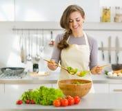 Lächelnde junge Hausfrau, die frischen Salat mischt lizenzfreies stockbild