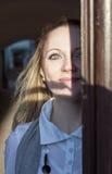 Lächelnde junge kaukasische blonde Frau, die aus dem Eingang mit Gesichts-halbem Lit und teilweise im Schatten heraus schaut Stockfoto