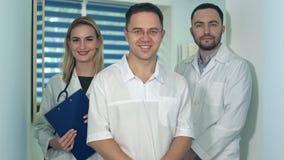 Lächelnde junge medizinische Arbeitskräfte, die für die Kamera aufwerfen Stockbild