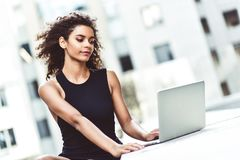 Lächelnde junge Mischrassefrau, die ihren Laptop verwendet, um online zu plaudern lizenzfreie stockbilder