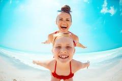 Lächelnde junge Mutter und Kind auf der Küste, die Spaßzeit hat lizenzfreie stockbilder