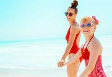Lächelnde junge Mutter und Kind im roten Badeanzug auf dem Strandgehen lizenzfreie stockfotografie