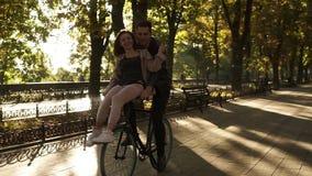 Lächelnde junge Paare, die auf das gleiche schwarze Fahrrad mit Sonnenhintergrundbeleuchtung auf dem Hintergrund fahren Mädchen s stock footage