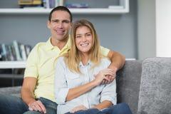 Lächelnde junge Paare, die auf ihrer Couch sitzen Lizenzfreies Stockbild
