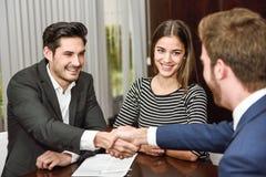 Lächelnde junge Paare, die Hände mit einem Versicherungsagenten rütteln