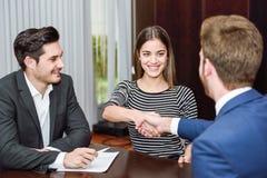Lächelnde junge Paare, die Hände mit einem Versicherungsagenten rütteln Lizenzfreie Stockfotos