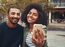 Lächelnde junge Paare, die selfie am intelligenten Telefon nehmen lizenzfreies stockfoto