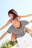 Lächelnde junge Paare, die Spaß am Strand haben Stockfotografie