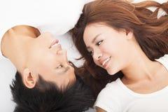 Lächelnde junge Paare, die zusammen liegen Stockfotografie