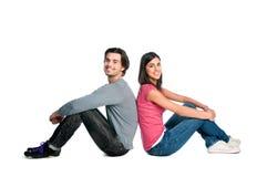 Lächelnde junge Paare, die zusammen sitzen Lizenzfreies Stockfoto
