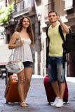 Lächelnde junge Paare mit dem Gepäck, das in Stadt geht Stockfoto