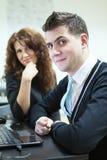 Lächelnde junge Paare mit dem Laptop, der Kamera betrachtet Stockfoto