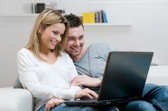Lächelnde junge Paare mit Laptop Stockbild