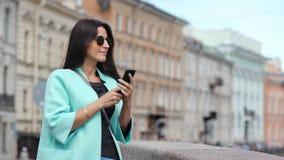 Lächelnde junge Reisefrau der Mode, die Foto unter Verwendung des Smartphone bewundert historische Architektur macht stock footage
