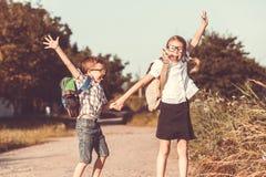Lächelnde junge Schulkinder in einer Schuluniform gegen einen Baum Stockbild