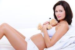 Lächelnde junge schwangere Frau mit Teddybärspielzeug Stockfoto