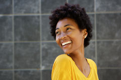 Lächelnde junge schwarze Frau, die über ihrer Schulter schaut Stockfoto