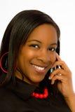 Lächelnde junge schwarze Frau, die auf Handy spricht. Lizenzfreies Stockfoto
