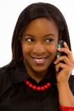 Lächelnde junge schwarze Frau, die auf Handy spricht. Stockfotos