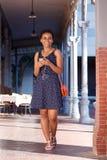 Lächelnde junge schwarze Frau, die mit Mobiltelefon und Kopfhörern geht stockfotografie