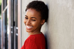 Lächelnde junge schwarze Frau, die sich draußen an der Wand lehnt Stockfotografie
