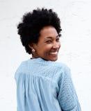 Lächelnde junge schwarze Frau, die zurück schaut Stockbild