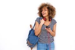 Lächelnde junge schwarze Frau mit Handykopfhörern und Tasche gegen weißen Hintergrund stockfoto