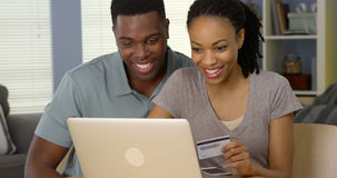 Lächelnde junge schwarze Paare unter Verwendung der Kreditkarte, zum von on-line-Käufen abzuschließen Lizenzfreie Stockfotografie