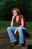Lächelnde junge Sitzfrau draußen Stockfotos