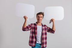 Lächelnde junge zufällige bubles Sprache der Holding zwei Lizenzfreie Stockbilder