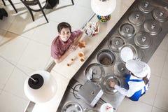 Lächelnde Jungen-kaufende Eiscreme von der Kellnerin At Counter Lizenzfreies Stockbild