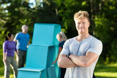 Lächelnde junger Mann-stehende Arme gekreuzt während Freunde, die Pyr machen Stockfoto