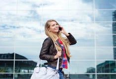 Lächelnde Jungereisefrau, die mit Tasche und Handy geht Lizenzfreie Stockfotografie