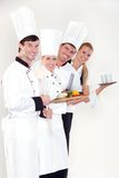 Lächelnde Köche und Kellnerin Stockfoto