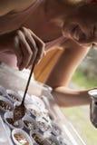 Lächelnde kaukasische Frau bereitet Schokoladengebäck zu Lizenzfreie Stockfotografie