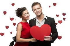 Lächelnde kaukasische Paare der Junge, die rotes Herz halten Stockbilder