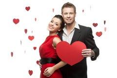 Lächelnde kaukasische Paare der Junge, die rotes Herz halten Lizenzfreies Stockfoto