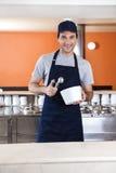 Lächelnde Kellner-Holding Scoop And-Schüssel in der Eisdiele Lizenzfreie Stockfotografie