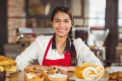 Lächelnde Kellnerin, die über Gebäck steht lizenzfreie stockbilder