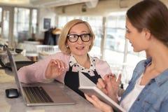 Lächelnde Kellnerin, die Arbeit mit ihrem Arbeitgeber bespricht Lizenzfreie Stockbilder