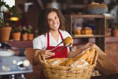 Lächelnde Kellnerin, die Brot von einem Korb aufhebt Lizenzfreie Stockfotos