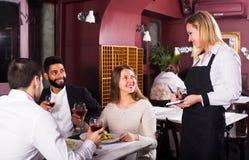 Lächelnde Kellnerin und Gäste am Tisch Lizenzfreies Stockbild
