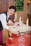 Lächelnde Kellnerin, welche die Tabelle einstellt Stockbild