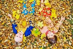 Lächelnde Kinder in den goldenen Blättern Lizenzfreie Stockbilder