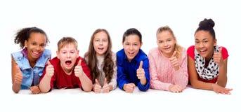 Lächelnde Kinder, die auf dem Boden liegen Stockfoto