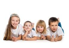 Lächelnde Kinder, die auf dem Boden liegen Stockbilder