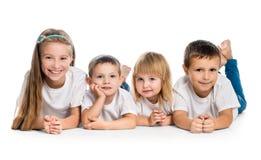 Lächelnde Kinder, die auf dem Boden liegen Lizenzfreie Stockfotos