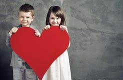 Lächelnde Kinder, die ein Herz halten Lizenzfreies Stockfoto